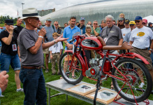 Photo of a man teaching folks about a motorcycle at the LeMay Vintage Motorcycle Festival